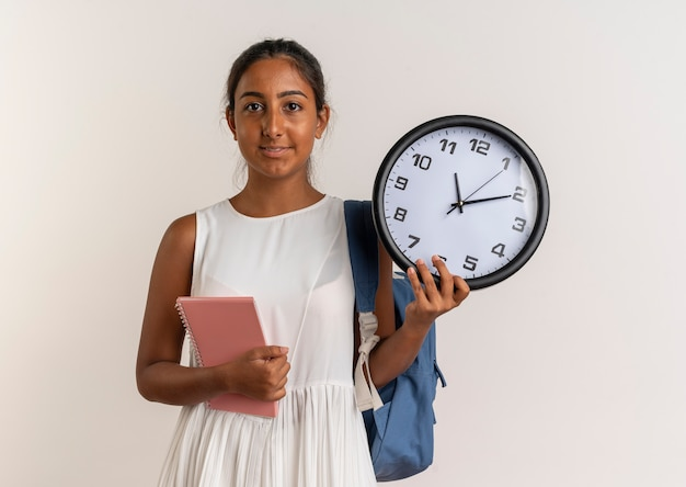 Jovem colegial satisfeita usando uma bolsa de costas segurando um caderno com um relógio de parede