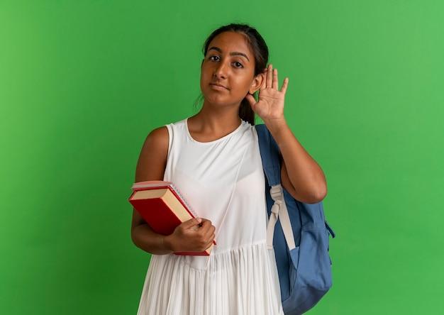 Jovem colegial usando mochila segurando livro com caderno e mostrando gesto de escuta