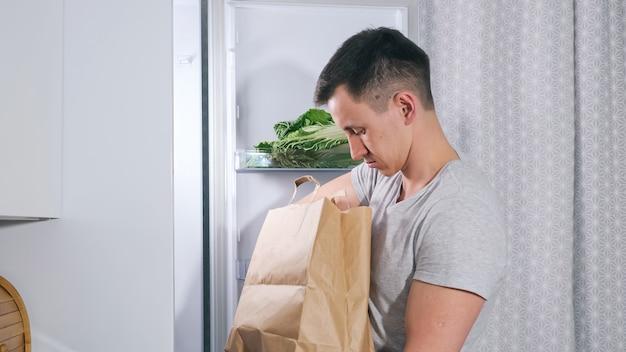 Jovem coloca diferentes produtos alimentícios em uma grande geladeira