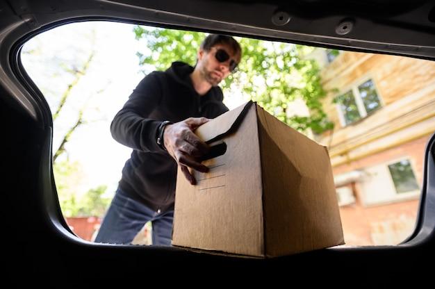 Jovem coloca uma caixa no carro