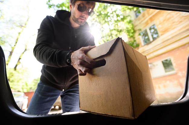 Jovem coloca uma caixa no porta-malas de um carro