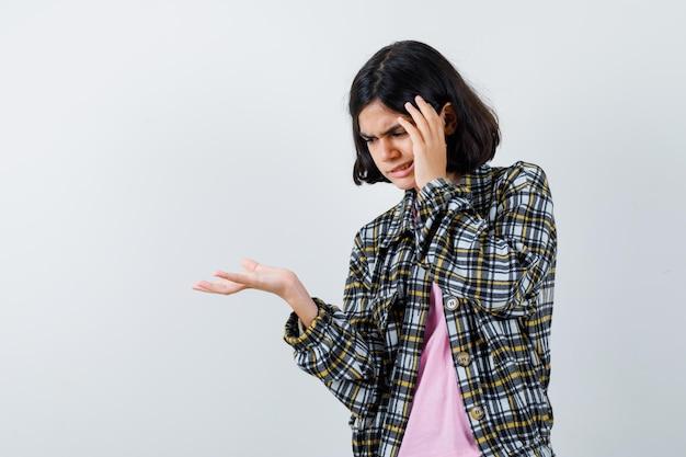 Jovem colocando a mão na têmpora e esticando a outra mão enquanto pensava em algo em uma camisa xadrez e camiseta rosa e parecia pensativa. vista frontal.