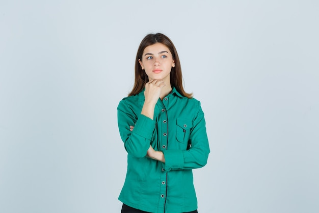 Jovem, colocando a mão para apoiar o queixo em uma camisa verde e olhando pensativa, vista frontal.