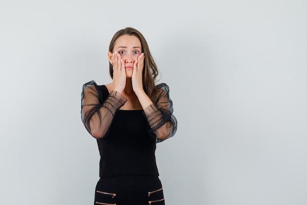 Jovem, colocando as mãos nas bochechas de blusa preta e calça preta e parecendo tímida, vista frontal.