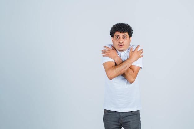 Jovem colocando as mãos nos ombros, tremendo de frio em uma camiseta branca e jeans e parecendo exausto, vista frontal.