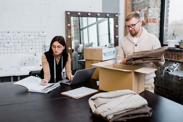 Jovem colocando calças dobradas em uma caixa de papelão enquanto empacota um pacote para um dos clientes enquanto seu colega faz um esboço