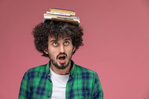 Jovem colocando livros na cabeça e olhando para eles