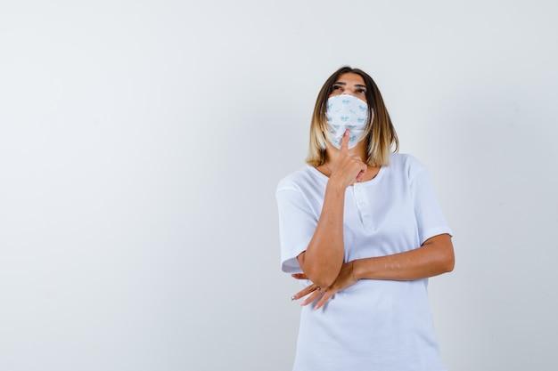 Jovem, colocando o dedo indicador sob o queixo, segurando a mão sob o cotovelo em uma camiseta branca e uma máscara e olhando pensativa. vista frontal.