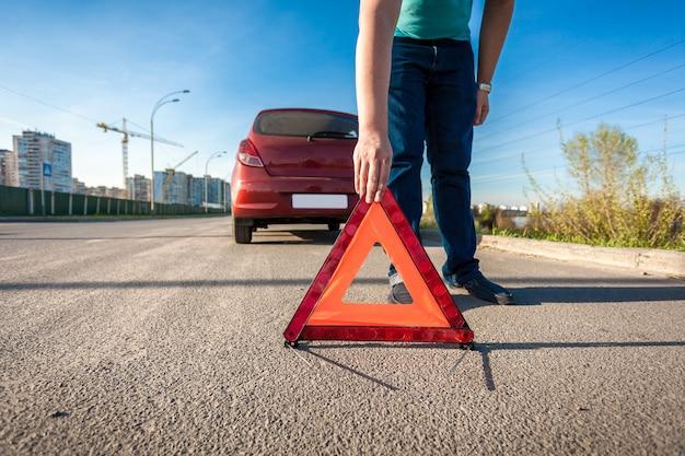 Jovem colocando um triângulo vermelho cantando na estrada após um acidente de carro