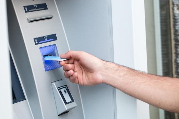 Jovem colocar seu cartão de crédito no caixa eletrônico