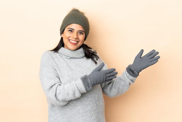 Jovem colombiana com chapéu de inverno isolado na parede bege, estendendo as mãos para o lado para convidar para vir