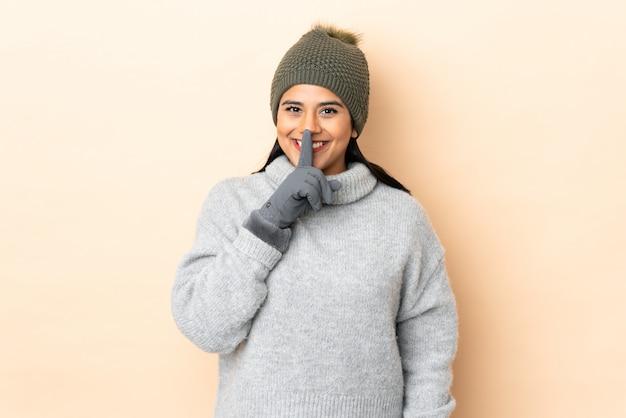 Jovem colombiana com chapéu de inverno isolado na parede bege, fazendo o gesto de silêncio