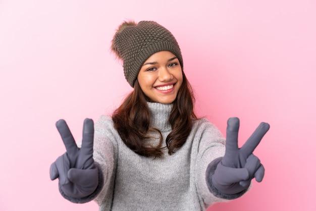 Jovem colombiana com chapéu de inverno sobre parede rosa isolada, sorrindo e mostrando sinal de vitória