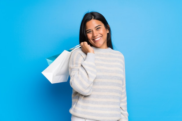 Jovem colombiana com suéter segurando um monte de sacolas de compras