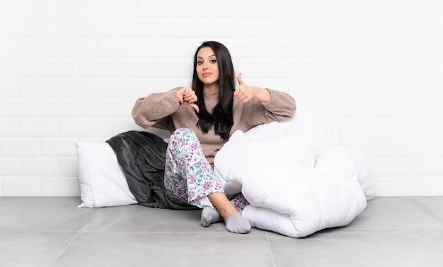 Jovem colombiana de pijama no interior fazendo sinal de bom-mau. indeciso entre sim ou não
