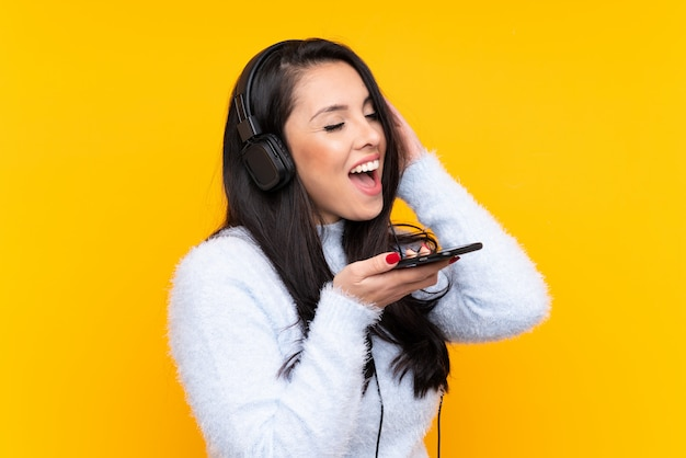 Jovem colombiana ouvindo música com um celular e cantando