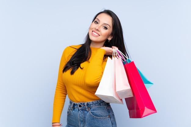 Jovem colombiana segurando sacolas de compras e sorrindo