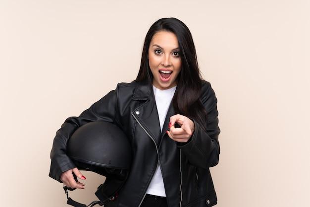 Jovem colombiana segurando um capacete de moto aponta o dedo para você