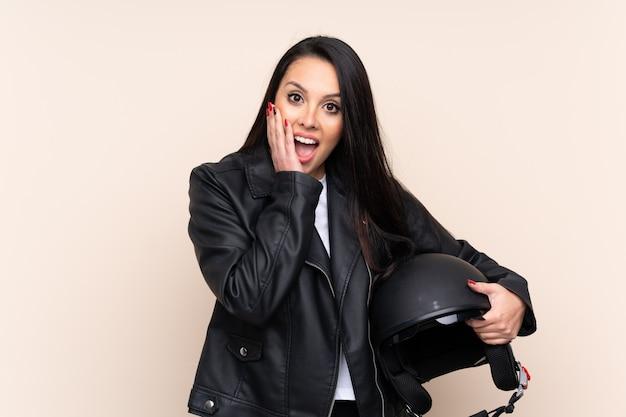Jovem colombiana segurando um capacete de moto com expressão facial de surpresa