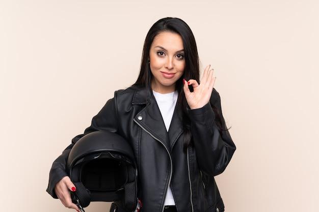 Jovem colombiana segurando um capacete de moto mostrando um sinal de ok com os dedos