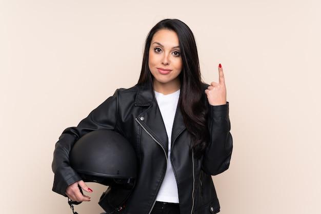 Jovem colombiana segurando um capacete de moto por cima da parede, apontando com o dedo indicador uma ótima idéia