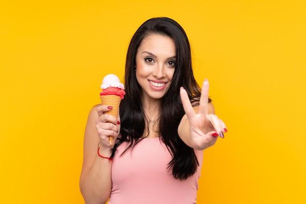 Jovem colombiana segurando um sorvete de corneta sobre parede amarela isolada, sorrindo e mostrando sinal de vitória