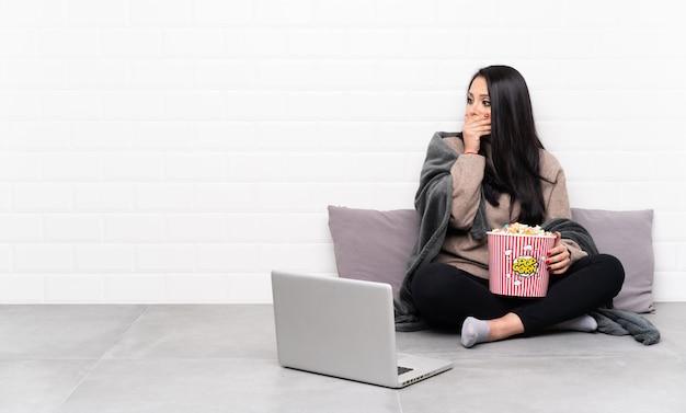 Jovem colombiana segurando uma tigela de pipocas e mostrando um filme em um laptop cobrindo a boca e olhando para o lado