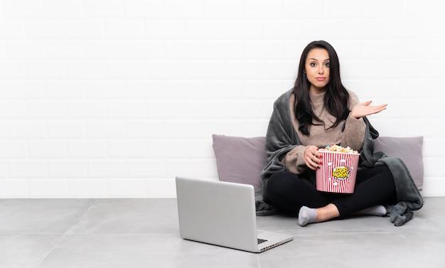 Jovem colombiana segurando uma tigela de pipocas e mostrando um filme em um laptop com dúvidas ao levantar as mãos