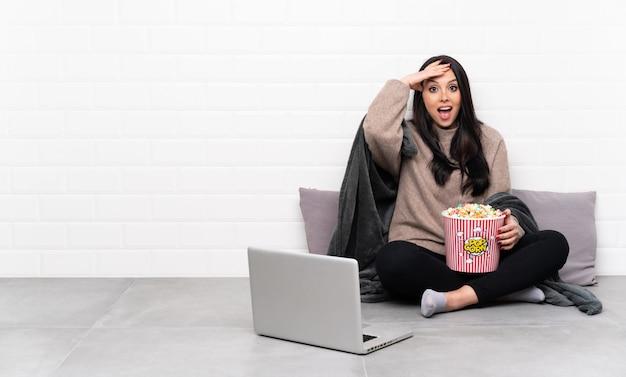 Jovem colombiana segurando uma tigela de pipocas e mostrando um filme em um laptop com expressão de surpresa
