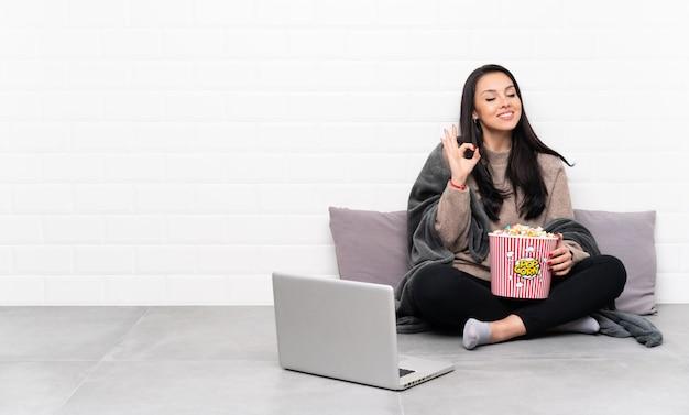 Jovem colombiana segurando uma tigela de pipocas e mostrando um filme em um laptop em pose zen