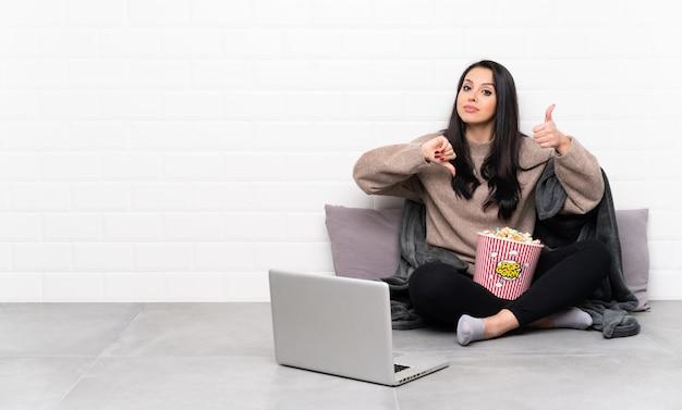 Jovem colombiana segurando uma tigela de pipocas e mostrando um filme em um laptop, fazendo sinal de bom-mau. indeciso entre sim ou não