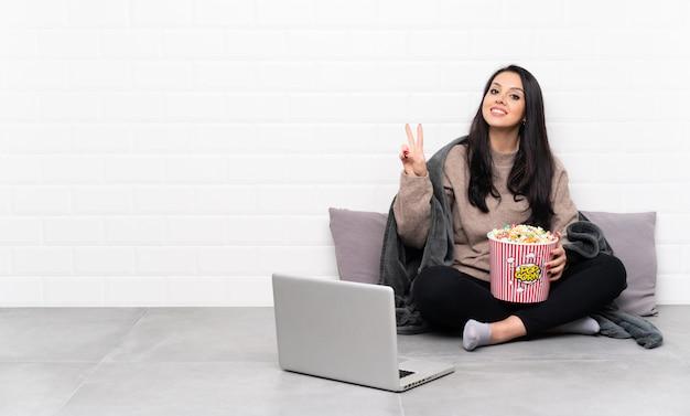 Jovem colombiana segurando uma tigela de pipocas e mostrando um filme em um laptop mostrando sinal de vitória com as duas mãos