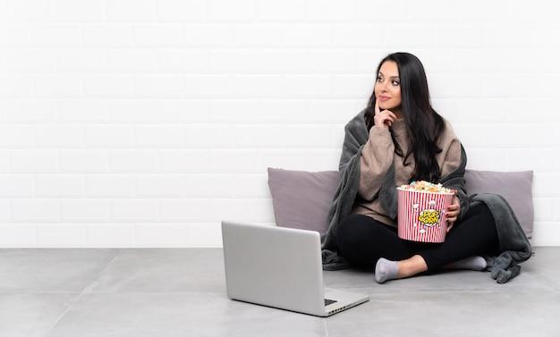 Jovem colombiana segurando uma tigela de pipocas e mostrando um filme em um laptop, pensando em uma idéia enquanto olha para cima
