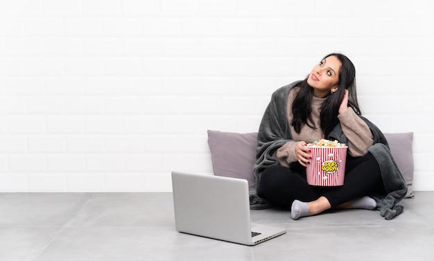Jovem colombiana segurando uma tigela de pipocas e mostrando um filme em um laptop, pensando em uma idéia