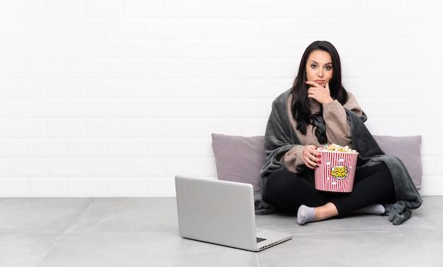 Jovem colombiana segurando uma tigela de pipocas e mostrando um filme em um pensamento de laptop