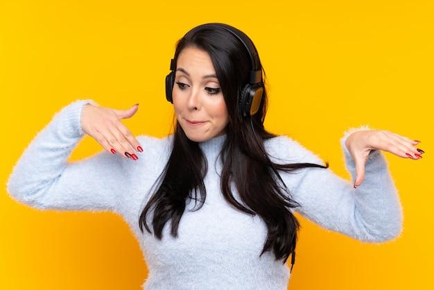Jovem colombiana sobre música e parede amarela isolada ouvindo e dançando