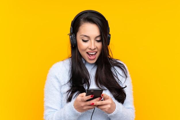 Jovem colombiana sobre ouvir música de parede amarela isolada e olhando para o celular