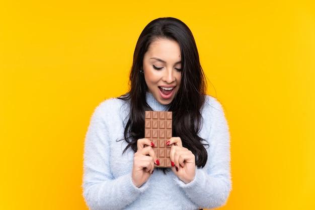 Jovem colombiana sobre parede amarela isolada, comendo uma tablete de chocolate