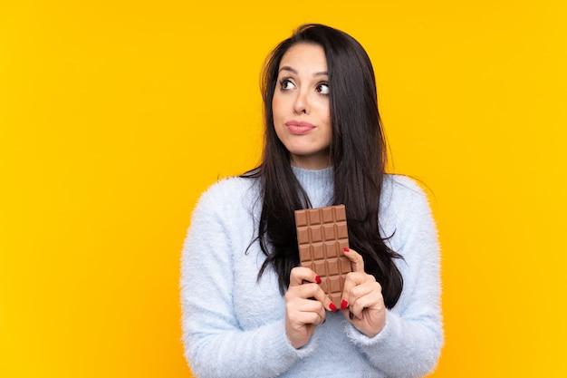 Jovem colombiana sobre parede amarela isolada, tomando uma tablete de chocolate e tendo dúvidas
