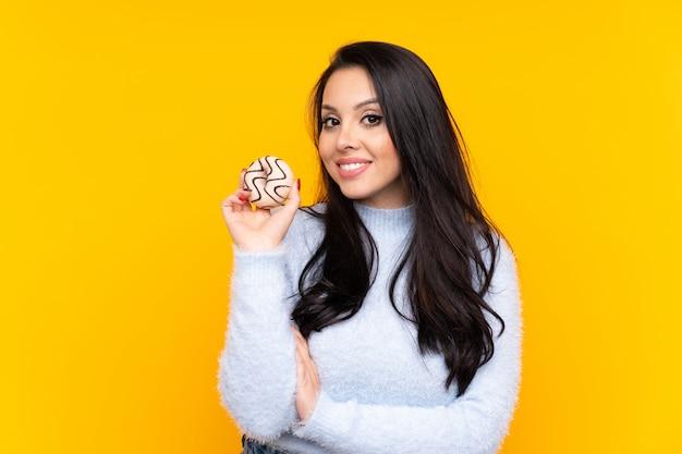 Jovem colombiana sobre parede amarela segurando uma rosquinha e feliz