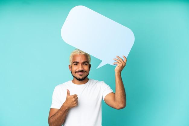 Jovem colombiano bonito isolado em um fundo azul segurando um balão de fala vazio com o polegar para cima