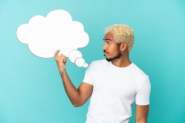 Jovem colombiano bonito isolado em um fundo azul segurando um balão de pensamento