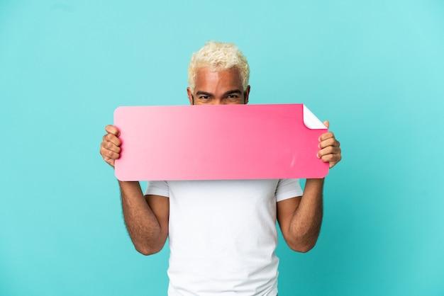 Jovem colombiano bonito isolado em um fundo azul segurando um cartaz vazio e se escondendo atrás dele