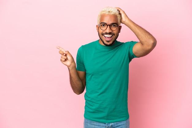 Jovem colombiano bonito isolado em um fundo rosa surpreso e apontando o dedo para o lado
