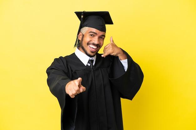 Jovem colombiano formado em faculdade, isolado em um fundo amarelo, fazendo gestos de telefone e apontando para a frente