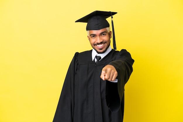 Jovem colombiano graduado pela universidade isolado em um fundo amarelo apontando o dedo para você com uma expressão confiante
