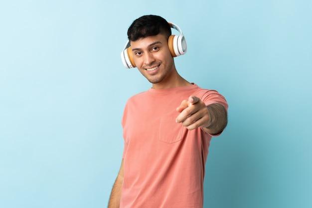 Jovem colombiano isolado ouvindo música azul e apontando para a frente