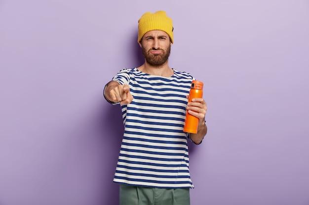 Jovem com a barba por fazer descontente aponta o dedo indicador para a câmera, segura uma garrafa térmica com bebida aromática, tem uma expressão sombria no rosto, usa um suéter listrado de marinheiro, isolado sobre o fundo roxo do estúdio