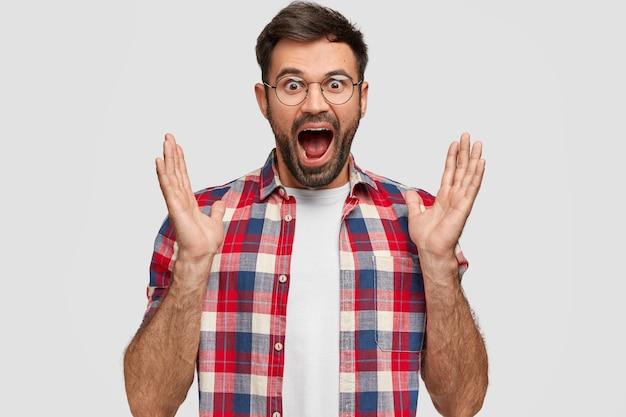 Jovem com a barba por fazer espantado aperta as mãos, abre a boca amplamente, percebe algo maravilhoso na frente, vestido com uma camisa xadrez, encostado na parede branca. conceito de pessoas e espanto