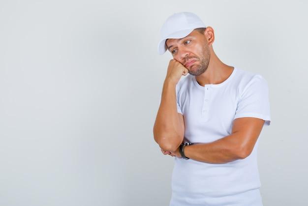 Jovem com a bochecha apoiada na mão levantada em uma camiseta branca, boné e parecendo triste e pensativo, vista frontal
